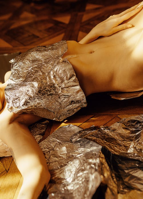 Woman in White Lace Panty Lying on Brown Wooden Floor