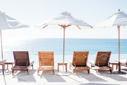 Two Brown Wooden Folding Chairs on White Sand Beach