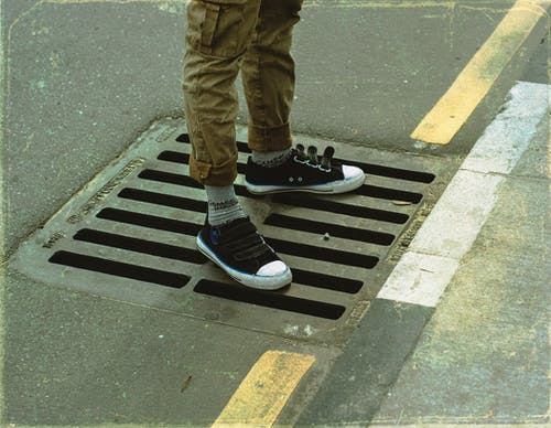 From above crop anonymous male legs in casual wear standing on asphalt road sewerage steel grating in daylight