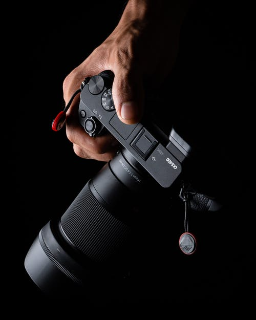 From above anonymous person holding modern professional photo camera with lens on black background