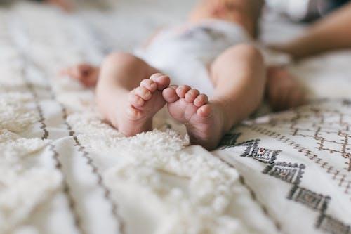 Bambino Sdraiato Sul Tessuto Bianco E Rosso