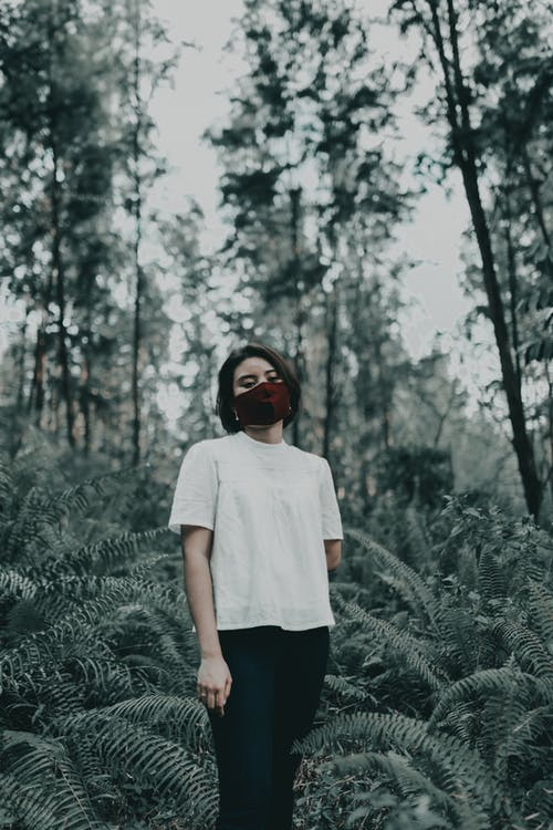 Emotionless woman in mask standing in forest