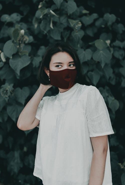 Calm young female in casual white shirt and protective face mask standing in lush park and touching hair while looking away