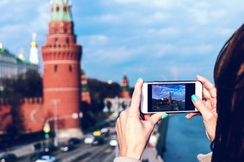 Person Holding White Android Smartphone Taking Photo of Tower