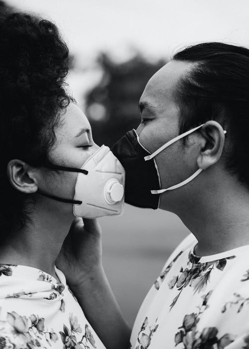 Grayscale Photo of Couple With Face Masks Kissing