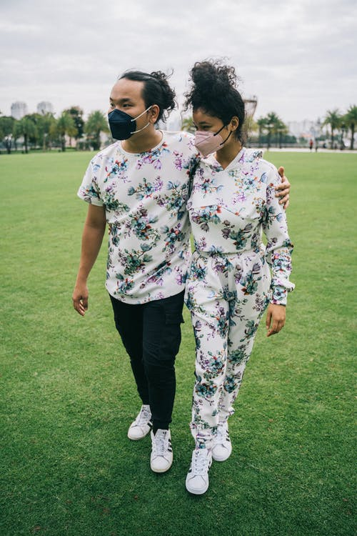 Couple with Face Masks Walking on Green Grass Field