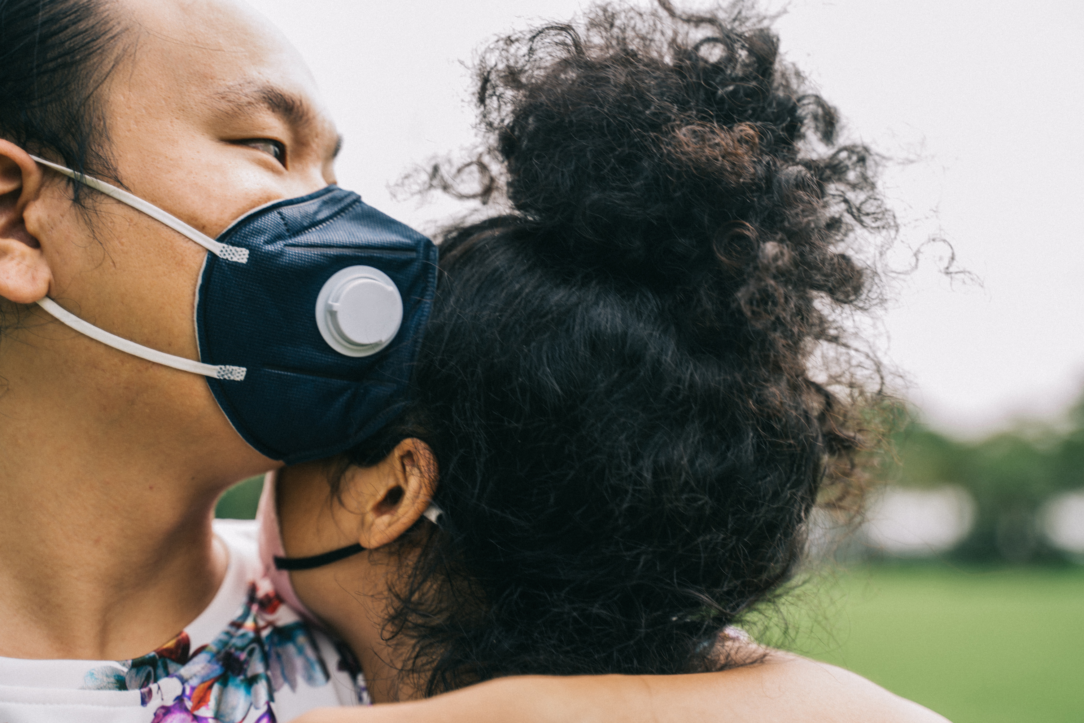 couple with face masks hugging
