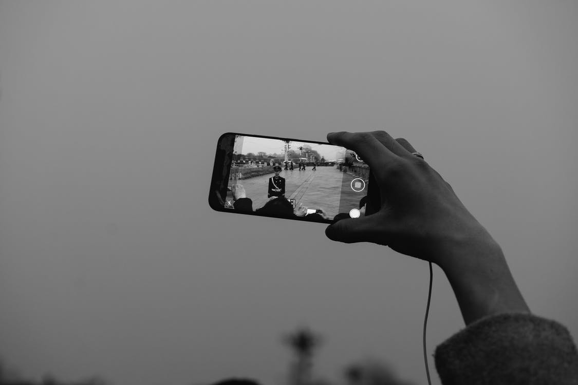 Grayscale Photo of Person Holding Iphone 6