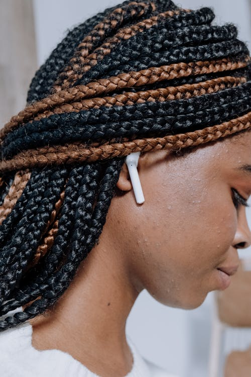 Woman With Braided Hair Wearing White Earbuds