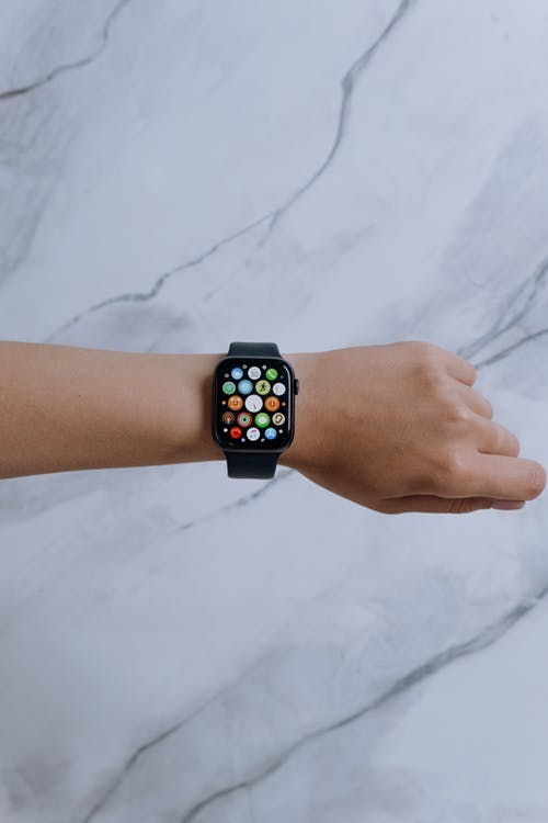Person Wearing Silver Aluminum Case Apple Watch With Blue Sport Band