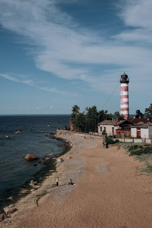 White and Red Lighthouse Near Body of Water