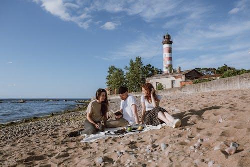 3 Women Sitting on Beach Shore