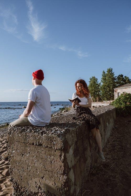 Man and Woman Sitting on Rock Near Sea