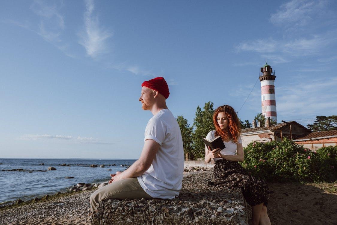 Man in White Shirt Sitting Beside Woman in White Shirt on Beach