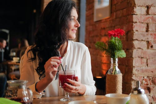 Happy young charming female in white elegant blouse with black wavy hair looking away with smile while drinking red sugary drink in transparent glass in cozy cafe with brown brick walls