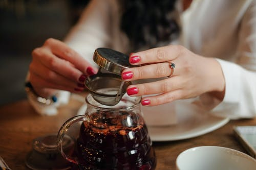 Unrecognizable female with ring on finger and bright manicure using small metallic sieve while making tea in bright cozy restaurant on blurred background