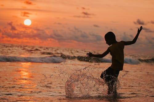 Man in White Shirt and Black Shorts Playing With Water during Sunset