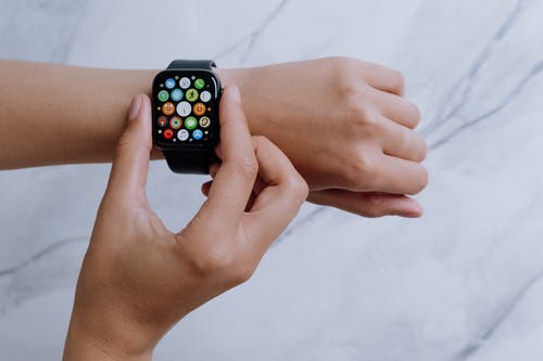 Person Wearing Silver Aluminum Case Apple Watch With White Sport Band