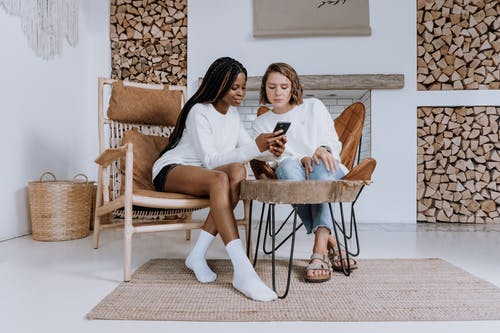 2 Women Sitting on Brown Wooden Chair