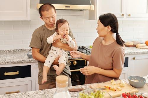 白いonesieで赤ちゃんを保持している茶色の乗組員の首のtシャツの男