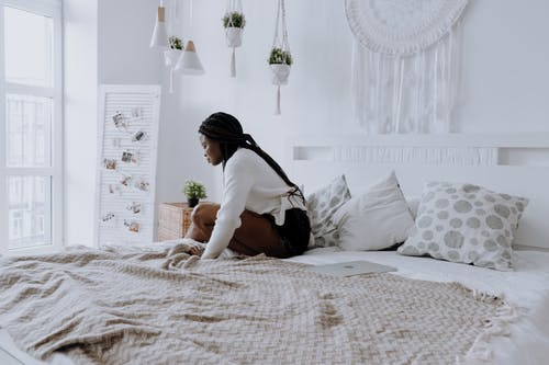 Woman in White Shirt and Black Skirt Sitting on Bed