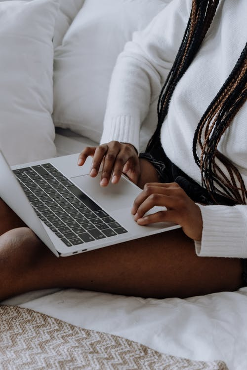 Woman in White Sweater Using Macbook Air