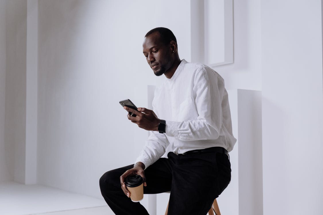 Man in White Dress Shirt and Black Pants Sitting on White Table