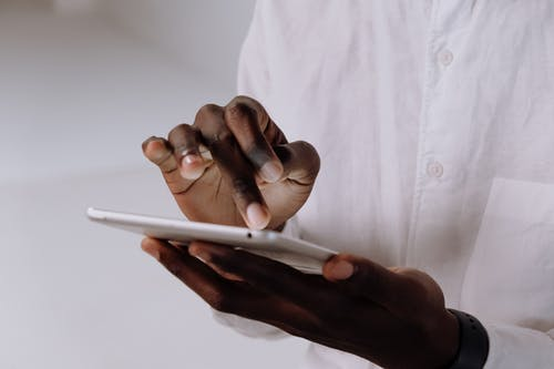 Person in White Dress Shirt Holding White Smartphone