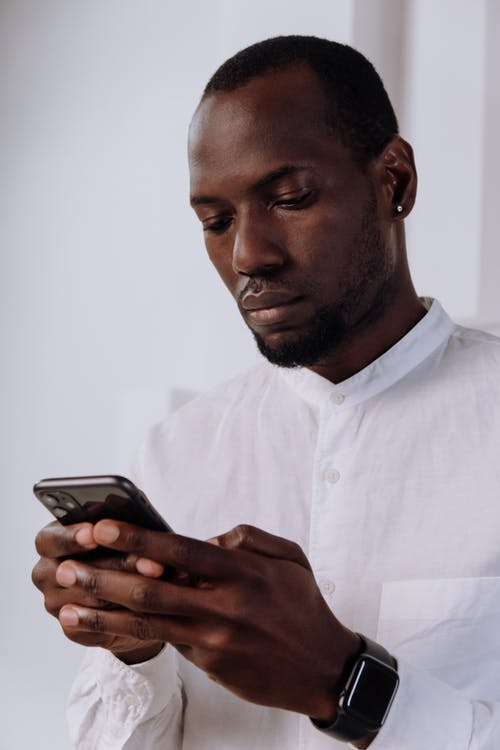 Man in White Dress Shirt Holding Black Smartphone