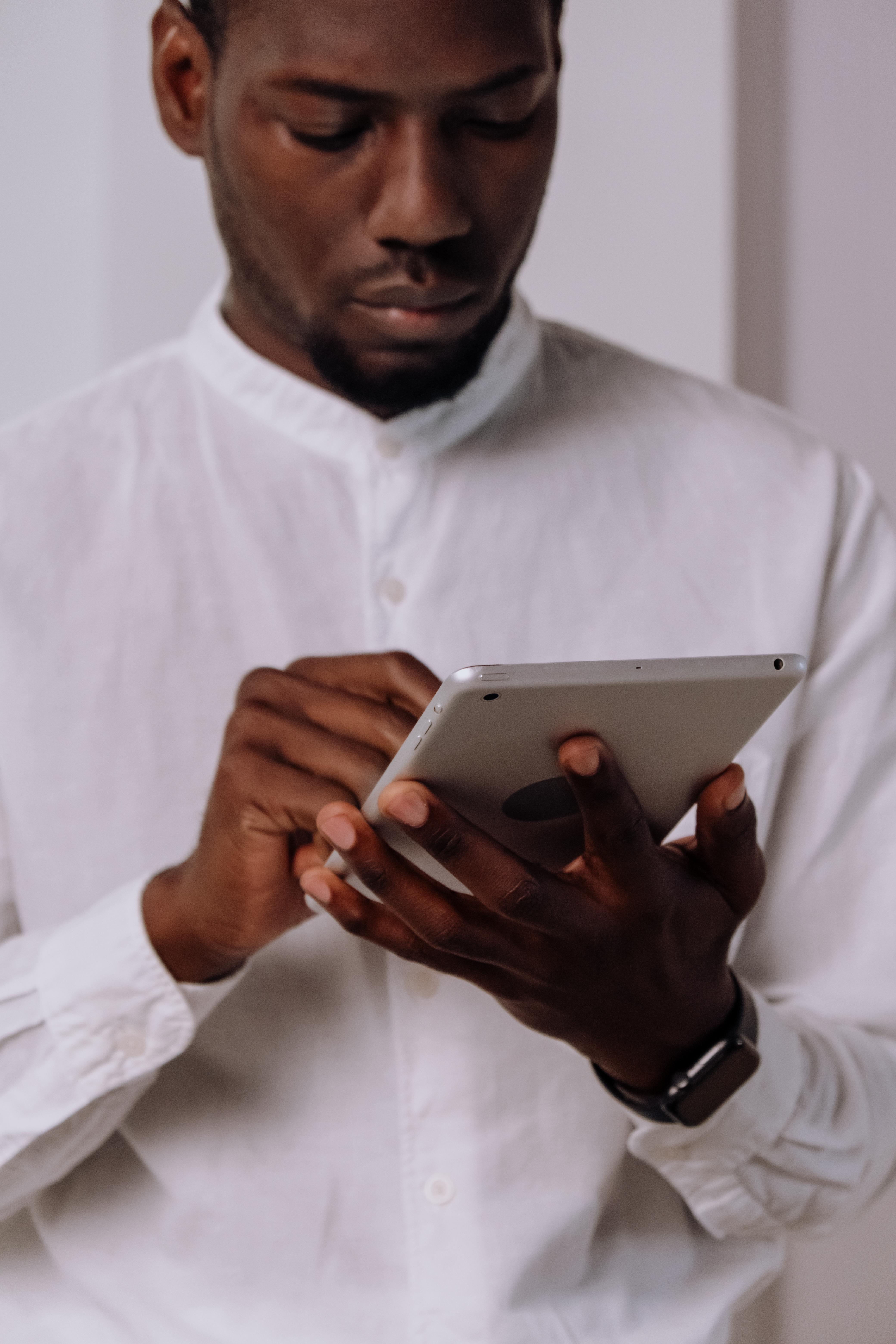 man in white dress shirt holding silver ipad