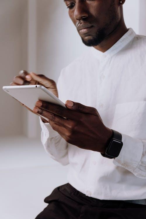Man in White Dress Shirt Holding White Tablet Computer