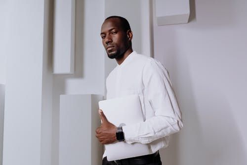 Man in White Dress Shirt Standing Beside White Wall