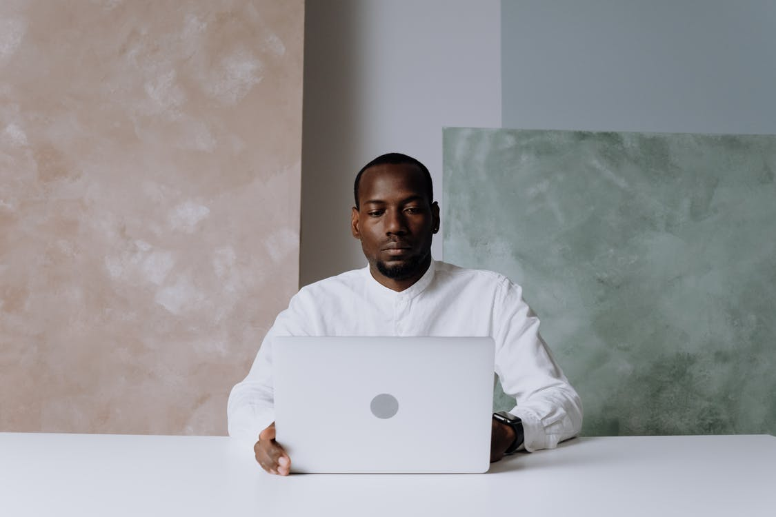 Man in White Long Sleeve Shirt Using Silver Macbook