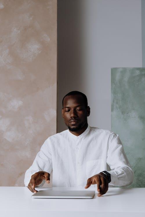 Man in White Dress Shirt Sitting Beside White Wall