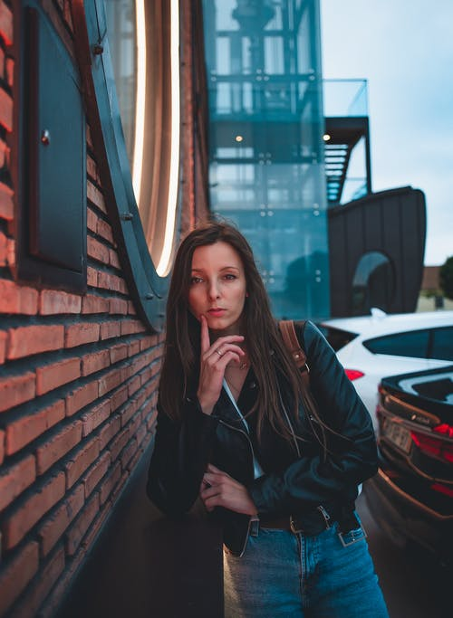 Woman in Black Leather Jacket Sitting on Chair