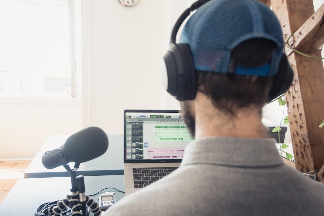 Man in Gray Sweater Wearing Blue Headphones