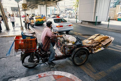 Full body side view of ethnic man carrying packages and cartons on tricycle while crossing asphalt road