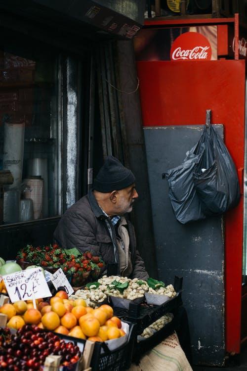 Elderly ethnic man selling fruits on street market