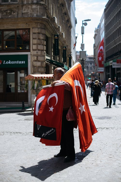 Old man selling red flags on street