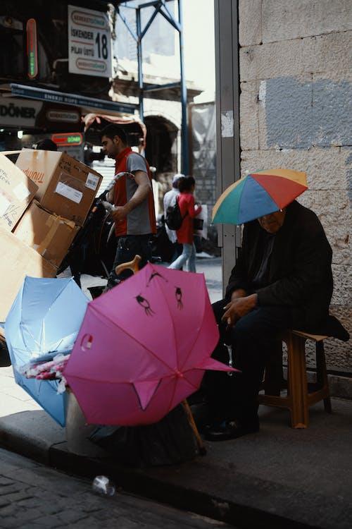 Old man in colorful umbrella on head selling umbrellas