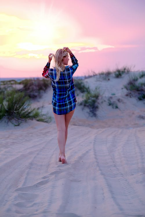 Alluring woman standing on sandy dunes in sunset light