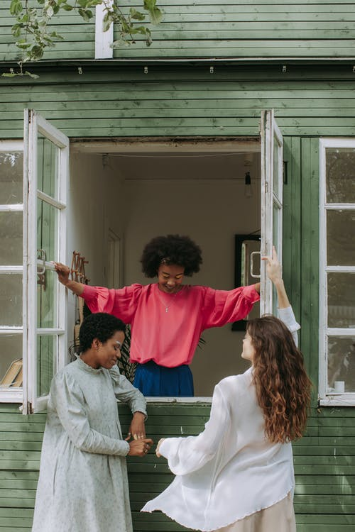 2 Women in Red Long Sleeve Shirt Standing Beside White Wooden Framed Glass Window