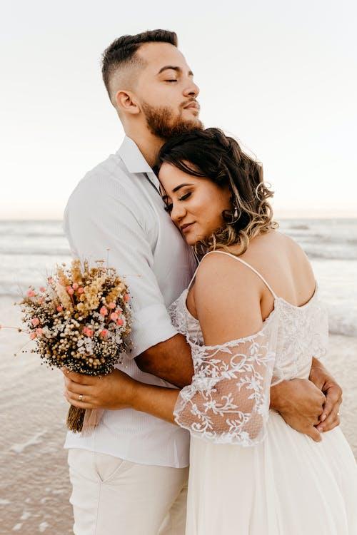 Newlywed couple embracing on beach