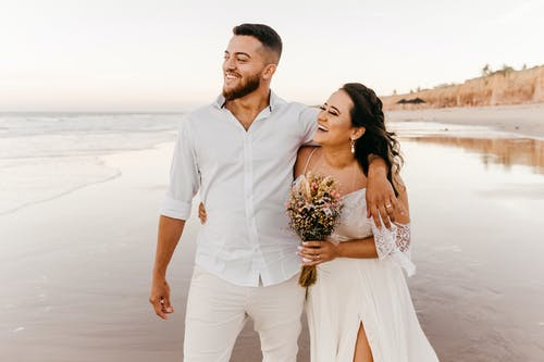 Smiling bearded groom in white shirt and trousers walking along sandy beach together with joyful bride in wedding dress