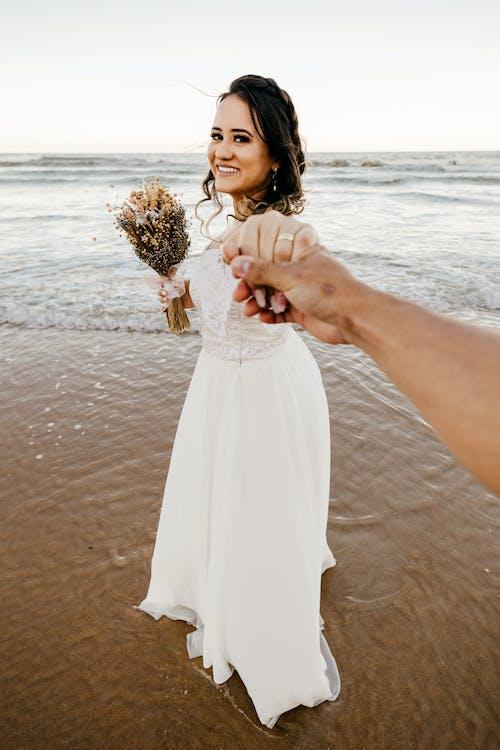 Bride in white dress standing on sandy beach