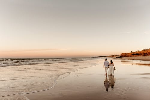 Back view of barefoot groom holding hand of bride in white dress and walking together on sandy coast