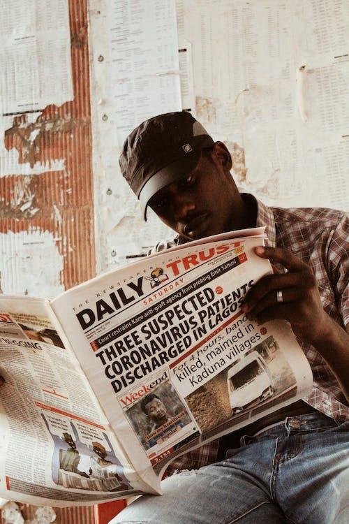Black man reading newspaper on street