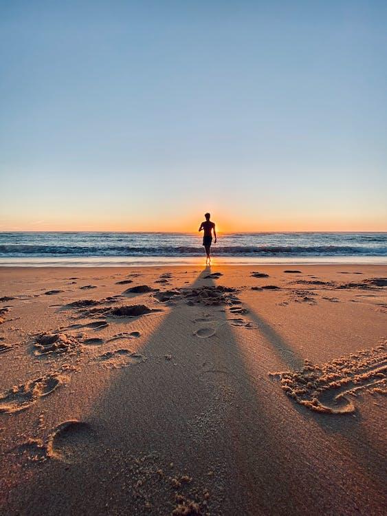 Woman in Black Jacket Walking on Beach
