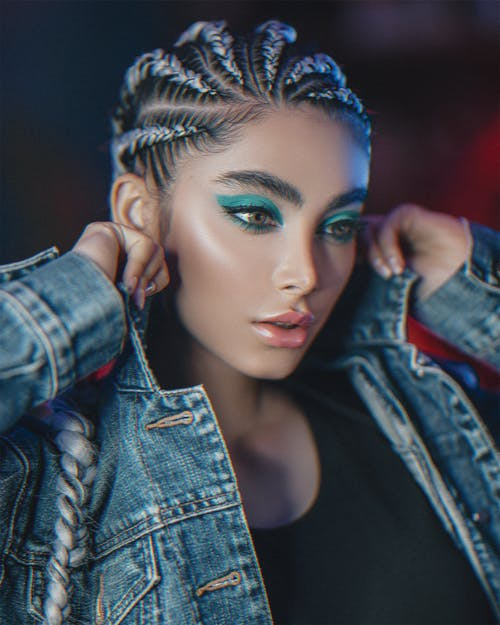 Young gorgeous female with vibrant makeup and cornrows looking down while adjusting collar of denim coat on blurred background