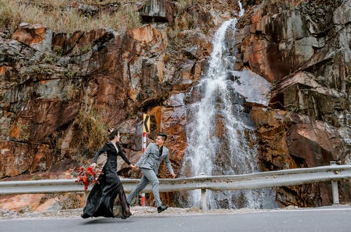 Full body of Asian happy cheerful bride and groom holding hands and running on concrete bridge near rocky stone cliff